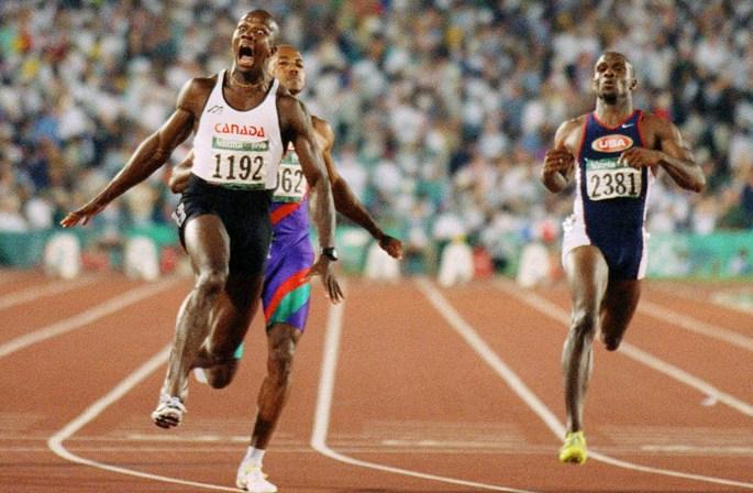 Donovan Bailey crie de joie après avoir passé le fil d'arrivé du 100 m