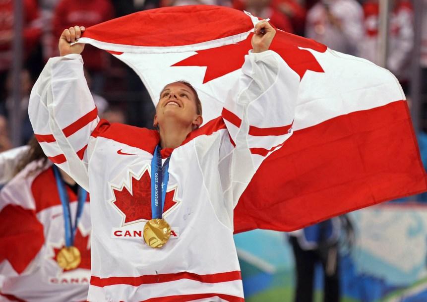 Kim St-Pierre, médaille au cou et tenant le drapeau du Canada