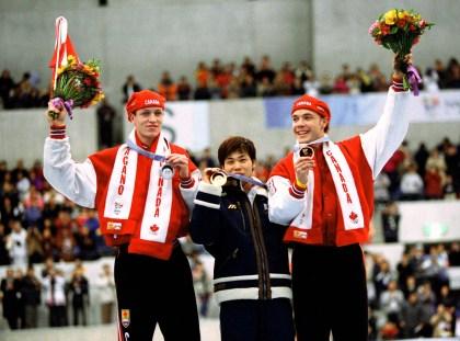 Jeremy Wotherspoon (gauche) et Kevin Overland (droite) du Canada célèbrent après avoir remporté respectivement des médailles d'argent et de bronze en patinage de vitesse longue piste aux Jeux olympiques d'hiver de Nagano de 1998. (Photo PC/AOC)