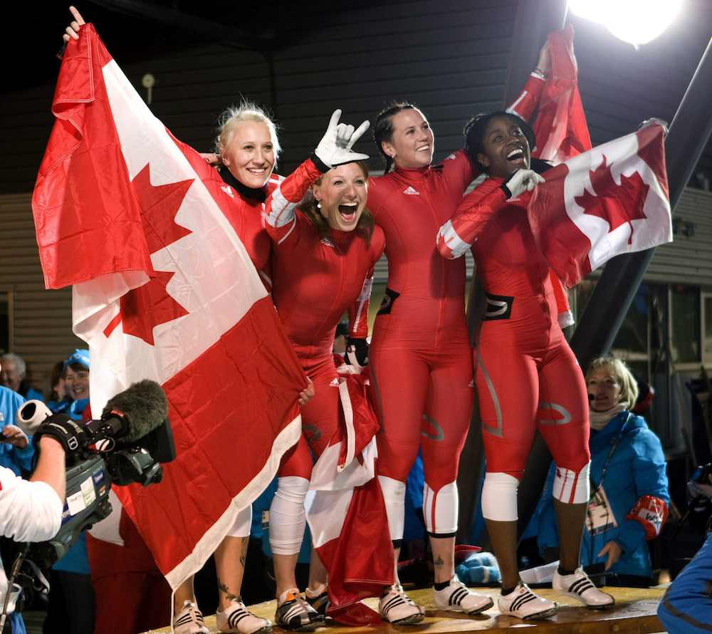 Les quatre Canadiennes célèbrent et portent plusieurs drapeaux canadiens