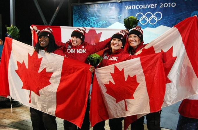 Les quatre Canadiennes montrent des drapeaux canadiens