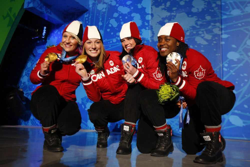 Les quatre Canadiennes accroupies montrent leur médaille.