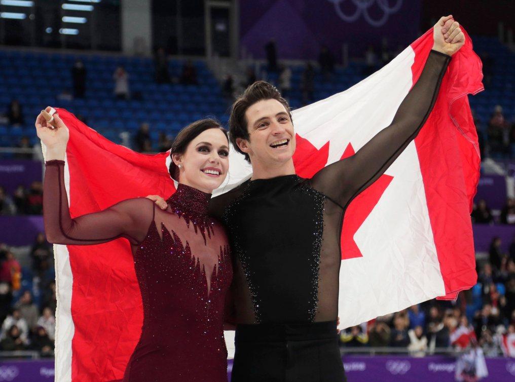Tessa Virtue et Scott Moir tiennent le drapeau canadien