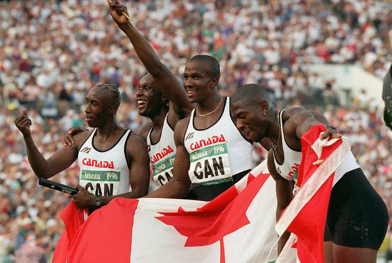 Quatre sprinteurs canadiens avec le drapeau du Canada