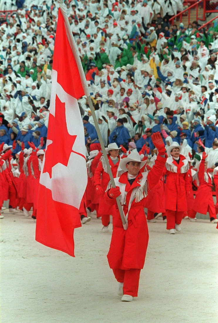 World figure skating champion Brian Orser carries the Canadian flag as he leads the Canadian Olympic team into McMahon Stadium in Calgary during the opening ceremonies of the XV Olympic Winter Games on February 13, 1988. THE CANADIAN PRESS/Paul Chiasson