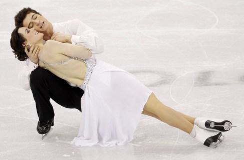 Tessa et Scott réalisent une figure, presque couchés sur la glace.