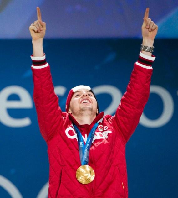 Alex Bilodeau, deux bras en l'air sur le podium et sa médaille d'or au cou