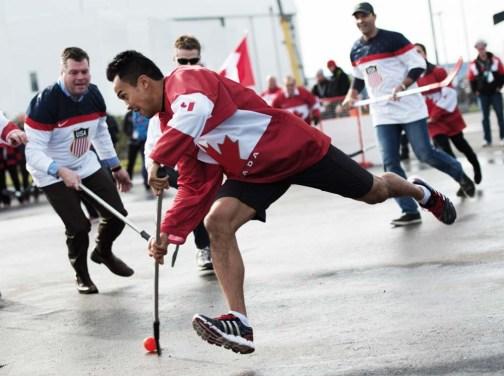 Le patineur de vitesse Gilmore Junio fait un lancer dans une partie amicale de hockey opposant le Canada et les États-Unis le 19 février 2014, aux Jeux olympiques d'hiver.