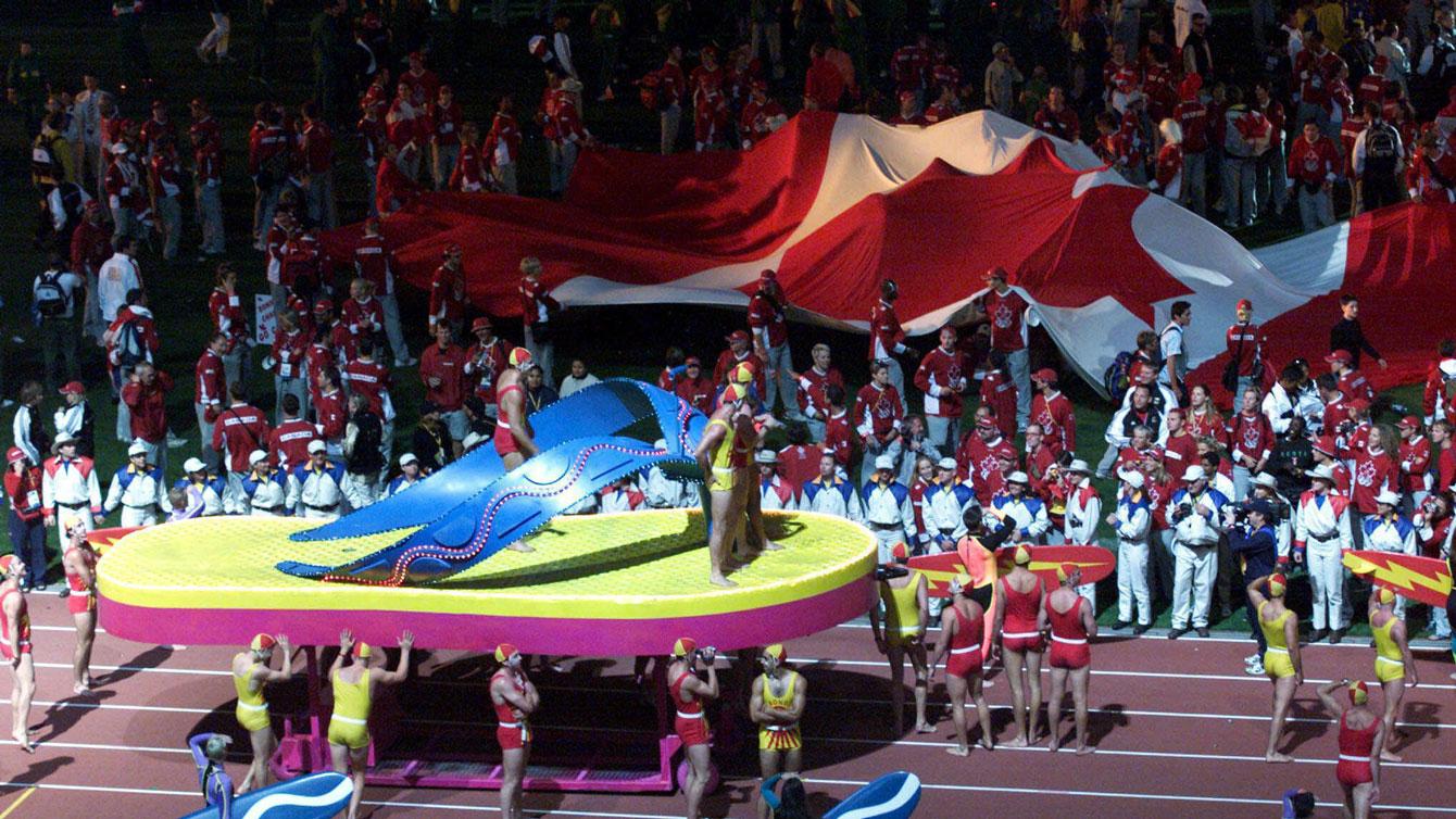 Les athlètes canadiens déroulent un drapeau géant lors de la cérémonie de clôture des Jeux de Sydney en 2000.