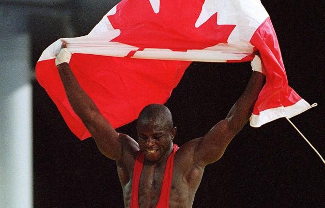 Canada's Daniel Igali waves the Canadian flag after winning the gold medal in wrestling at the 2000 Sydney Olympic Games. (CP Photo/ COC) Daniel Igali du Canada célèbre sa médaille d'or en lutte aux Jeux olympiques de Sydney 2000. (PC Photo/AOC)