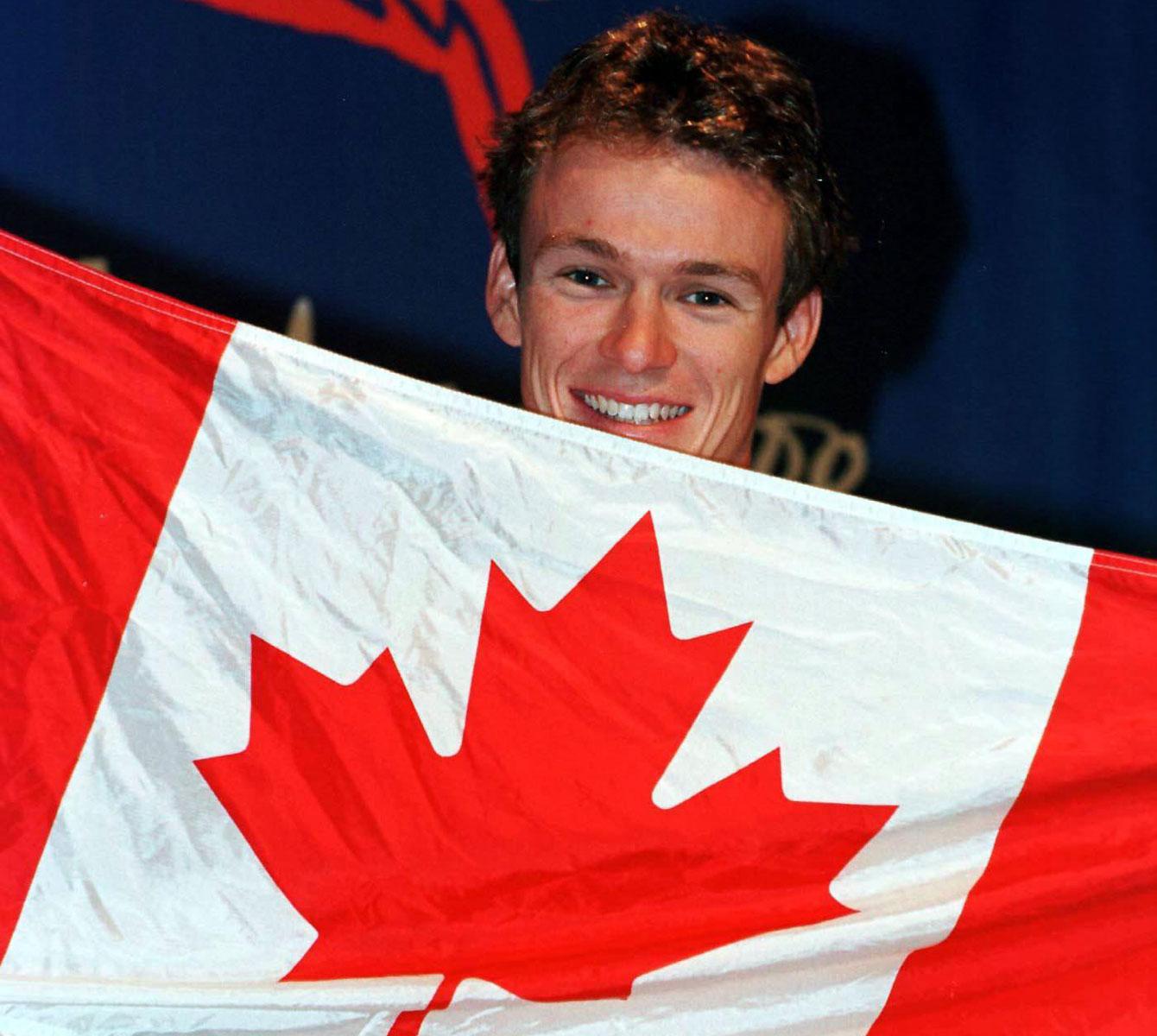 Simon Whitfield avec le drapeau canadien aux Jeux de Sydney.