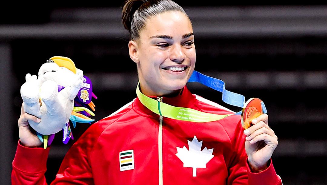 Une boxeuse sur le podium montre sa médaille