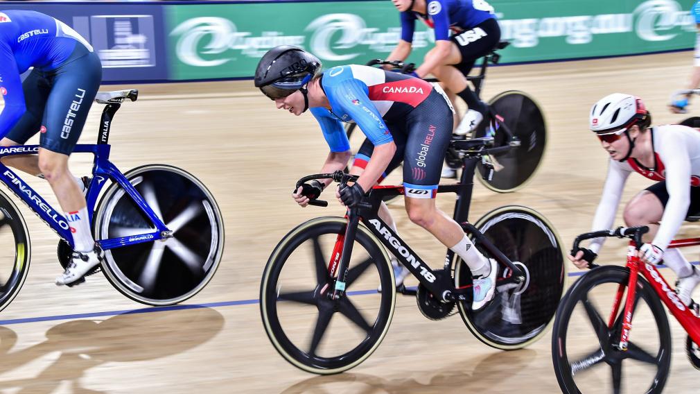 Des cyclistes disputent une épreuve d'omnium dans un vélodrome.