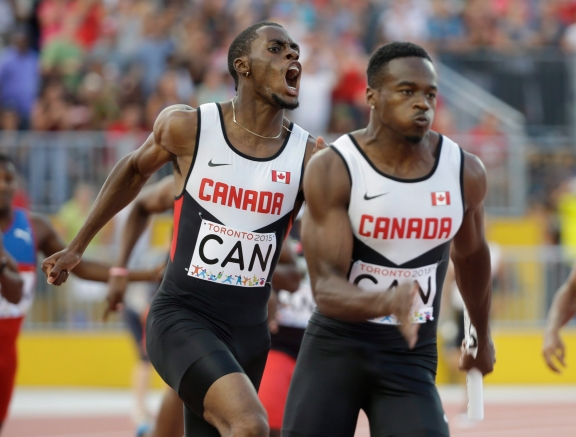 Canada's Brendon Rodney, left, screams after handing off the baton to Aaron Brown in the finals of the men's 4x100 meter relay at the Pan Am Games in Toronto, Saturday, July 25, 2015. Canada won the gold medal. (AP Photo/Mark Humphrey)