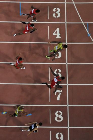 Andre De Grasse (couloir neuf) se penche pour capturer le bronze alors que Usain Bolt (5) et Justin Gatlin (7) se battent pour l'or et l'argent dans les derniers moments de la finale du 100 m aux Championnats du monde d'athlétisme de l'IAAF à Beijing en Chine le 23 août 2015.