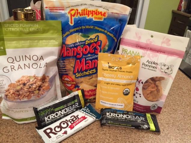 Collations assorties: mangues et pommes séchées, granola de quinoa pour le déjeuner, amandes et barres de protéine