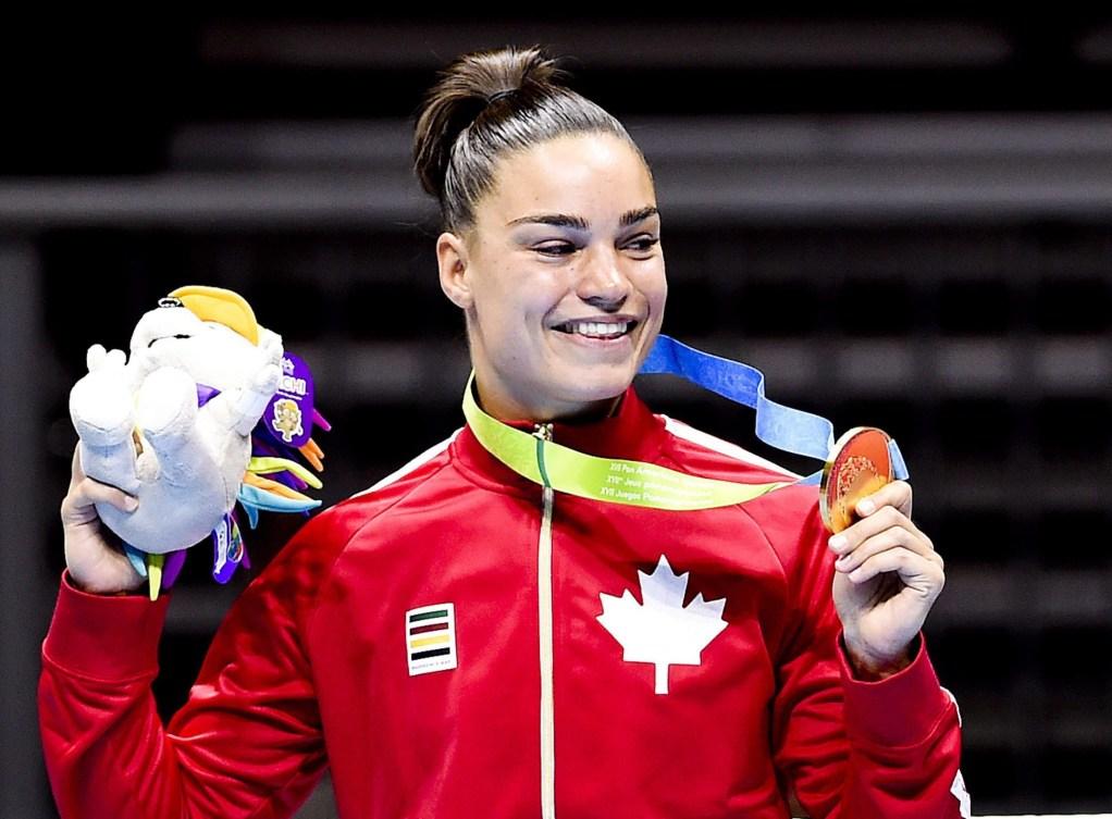 Une boxeuse montre sa médaille sur le podium
