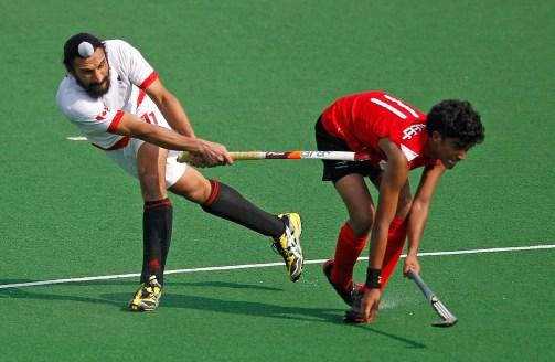 Karleef Abdullah Sasi de Singapour (droite) reçoit un coup de crosse dans les côtes gracieuseté du Canadien Jagdish Gill durant un match a New Delhi en Inde, le 21 février 2012. (AP Photo/Saurabh Das)