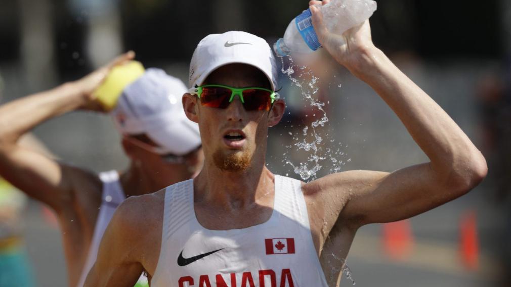 Un athlète s'arrose d'eau en pleine course