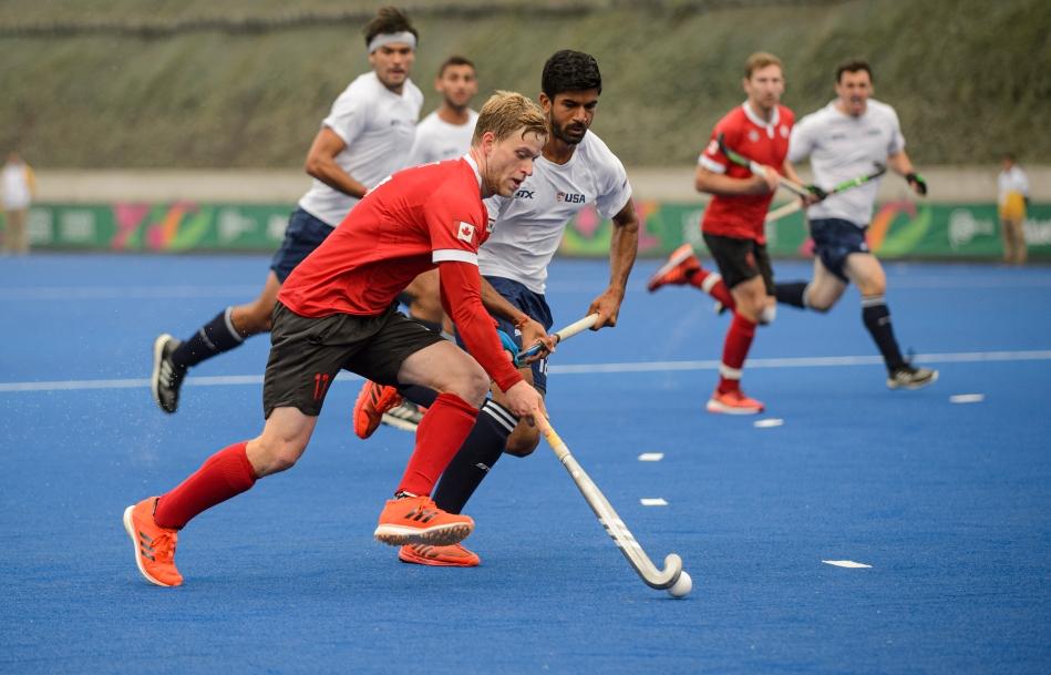 Un joueur canadien joue avec la balle en évitant un adversaire.