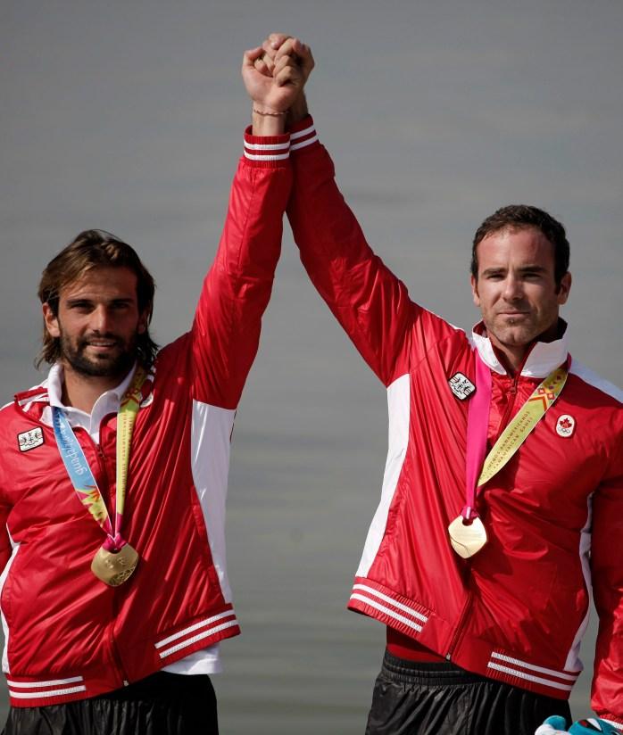 Les médaillés d'or Hugues Fournel et Ryan Cochrane du Canada, célébrant sur le podium lors de la cérémonie de remise des médailles au K-2 200 m aux Jeux panaméricains de 2011 au Mexique. (AP Photo/Eduardo Verdugo)