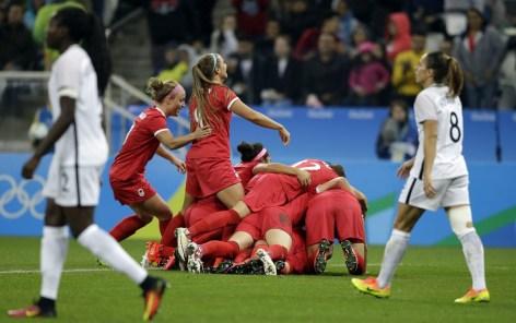 Les Canadiennes célèbrent le but de Sophie Schmidt dans le match du Canada contre la France en quarts de finale du tournoi féminin aux Jeux olympiques de Rio, le 12 août 2016.(AP Photo/Nelson Antoine)
