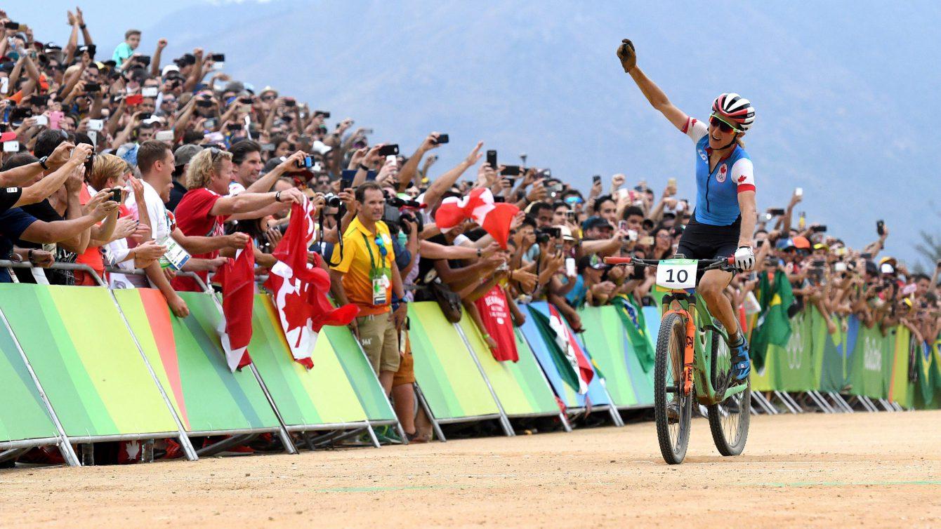 Une cycliste salue la foule à la fin de sa course