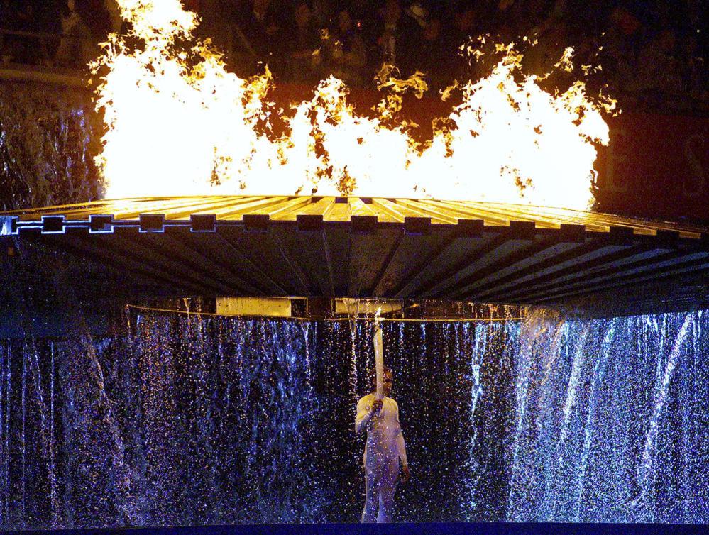 Cathy Freeman se tient sous la flamme olympique lors de la cérémonie d'ouverture des Jeux olympiques de Sydney 2000.