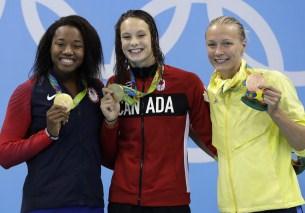 Les médaillées d'or du 100 m style libre Simone Manuel (gauche) et Penny Oleksiak (centre) avec la médaillée de bronze Sarah Sjostrom (droite) posent pour un photographe lors de la cérémonie des médailles. Jeux de Rio, 11 août 2016. (AP Photo/Michael Sohn)