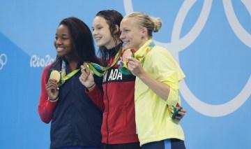 Penny Oleksiak (centre) sur le podium avec sa médaille d'or du 100 m libre aux Jeux de Rio, en compagne de Simone Manuel (or,gauche) et Sarah Sjostrom (bronze, droite). Photo Jason Ransom/COC