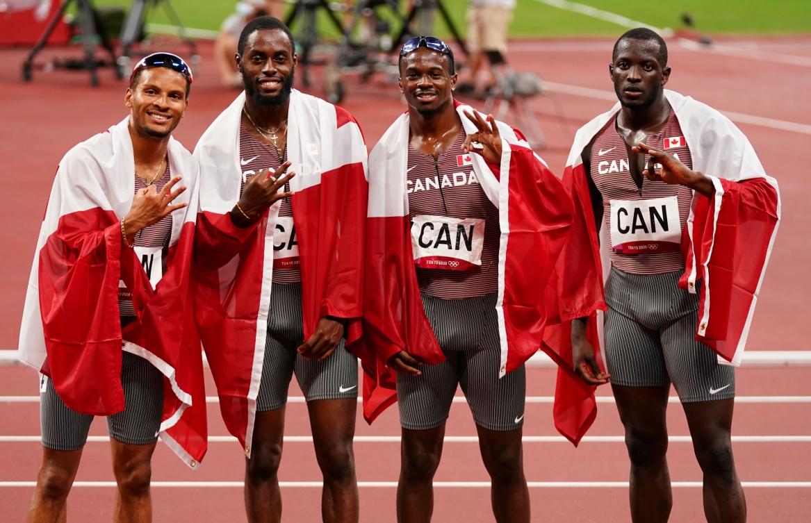 L'équipe du relais masculin 4x100 m pose avec des drapeaux canadiens.