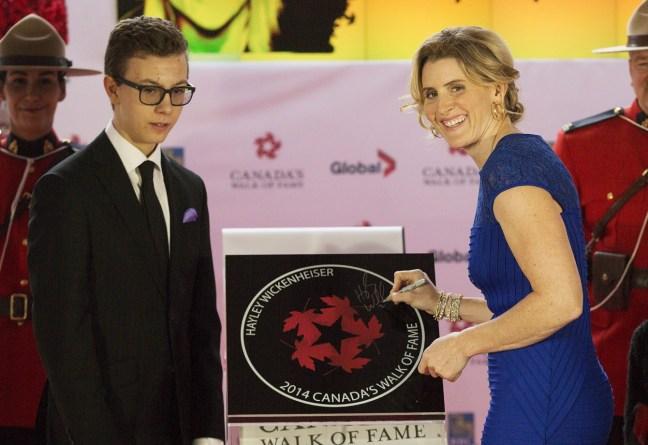 Avec l'aide de son fils Noah Pacina, l'athlète olympique de hockey Hayley Wickenheiser, à droite, est intronisée au Panthéon des sports canadiens à Tornto, le 18 octobre 2014. LA PRESSE CANADIENNE / Michelle Siu