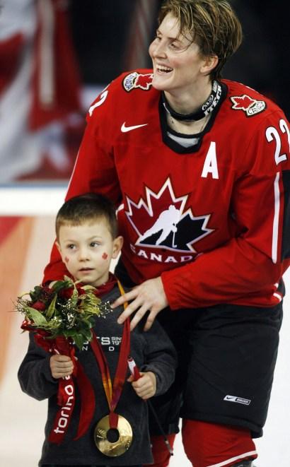 Hayley Wickenheiser du Canada, et son fils Noah pendant la cérémonie des médailles aux Jeux olympiques d'hiver de 2006, le 20 février 2006 , À Turin, en Italie. (AP Photo / Gene J. Puskar)