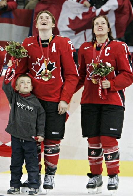 Hayley Wickenheiser du Canada, à gauche, son fils Noah et Cassie Campbell, lèvent les yeux tandis qu'ils élèvent le drapeau canadien pendant la cérémonie des médailles aux Jeux olympiques d'hiver de 2006, le 20 février 2006 , À Turin, en Italie. (AP Photo / Gene J. Puskar)