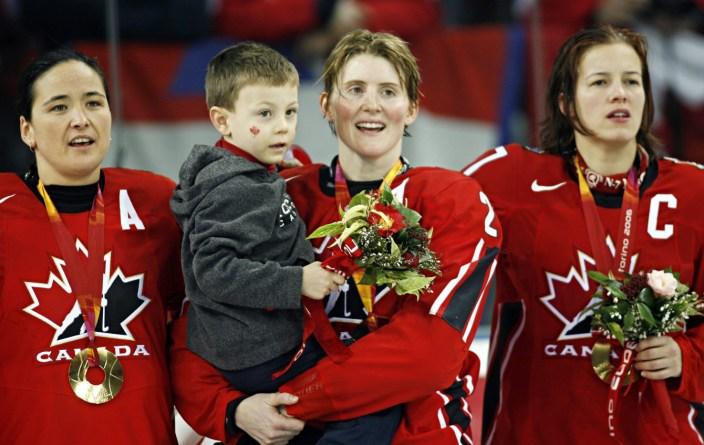 Hayley Wickenheiser d'Équipe Canada tient son fils, Noah, et chante l'hymne avec Vickey Sunohara, à gauche, et Cassie Campbell, à droite, fête après avoir vaincu la Suède 4-1 pour remporter la médaille d'or aux Jeux olympiques de 2006, le 20 février 2006 à Turin. (CP PHOTO / Ryan Remiorz)