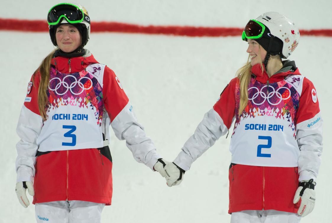 Les deux soeurs se tiennent la main sur le podium