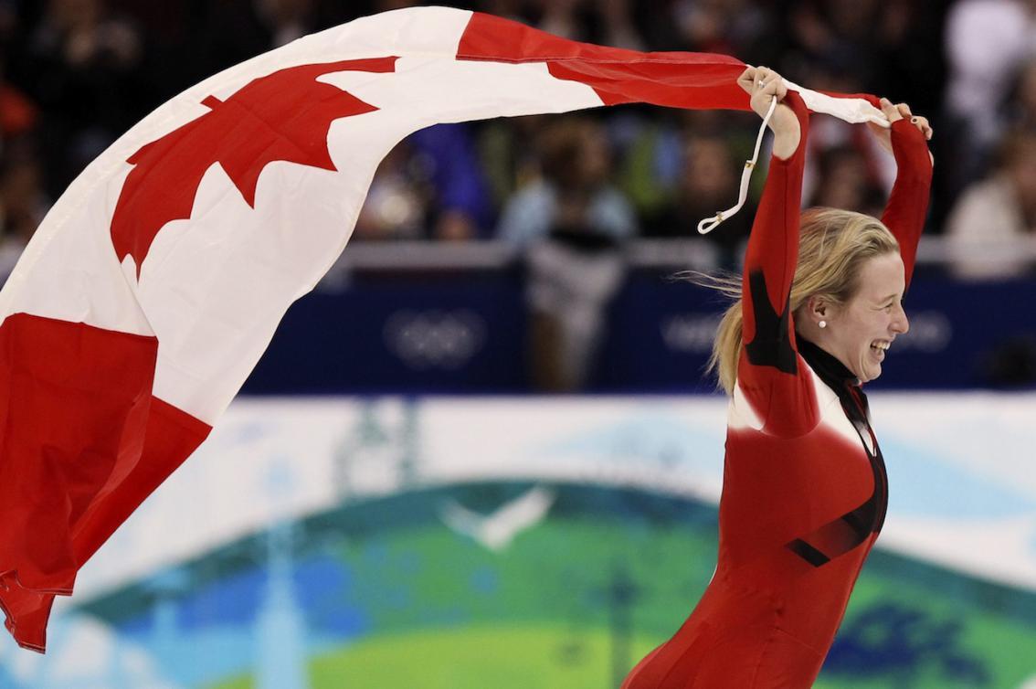 marianne St-Gelais fait un tour de piste sur la glace en portant le drapeau canadien, è Vancouver 2010.