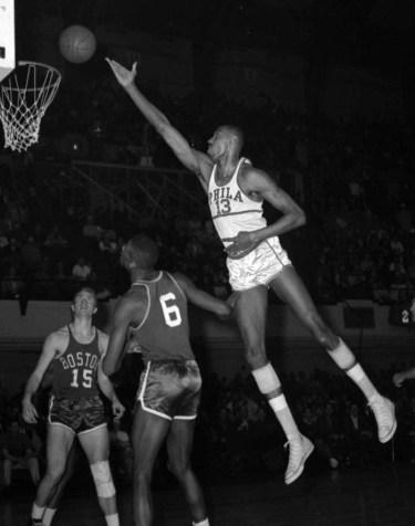Wilt Chamberlain complète un panier au dessus des défenseurs de Philadelphie en 1960. (AP Photo/File)