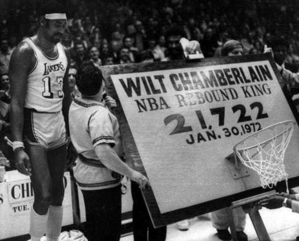 Wilt Chamberlain, à gauche, se tient à côté d'un panneau et d'un trophée qui lui ont été présenté après qu'il soit devenu le meilleur rebondeur de l'histoire de la NBA, à Los Angeles, le 31 janvier 1972.( AP Photo / file )