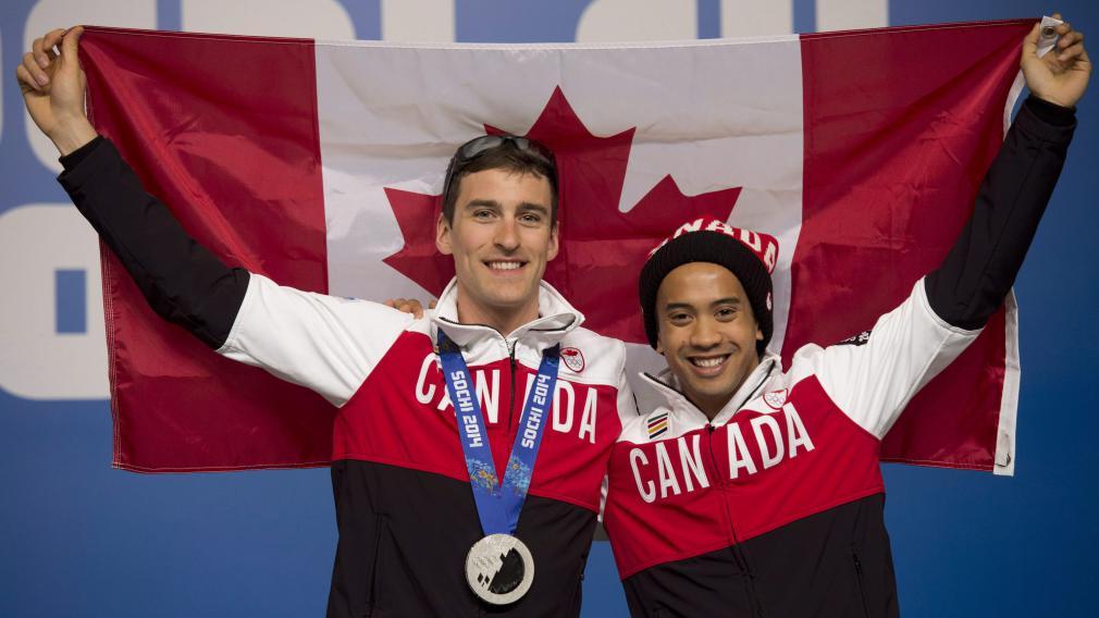 Gilmore Junio posant avec Denny Morrison, tenant le drapeau canadien
