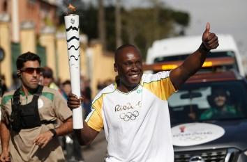 Bruni Surin court avec la flamme olympique avant les Jeux olympiques de Rio 2016.