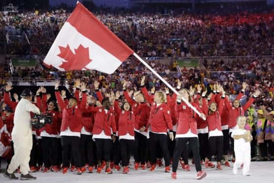 Rosie MacLennan porte le drapeau du Canada lors de la cérémonie d'ouverture des Jeux olympiques d'été de 2016 à Rio de Janeiro, au Brésil, le vendredi 5 août 2016. (Photo AP / David J. Phillip)