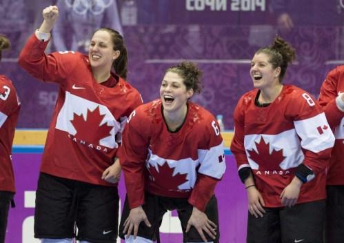 Lauriane Rougeau, Rebecca Johnston et Laura Fortino, de gauche à droite, célèbrent après avoir battu les États-Unis 3-2 en prolongation pour remporter la médaille d'or en finale de hockey féminin aux Jeux olympiques d'hiver de Sotchi, le jeudi 20 février 2014 à Sotchi. LA PRESSE CANADIENNE / Paul Chiasson