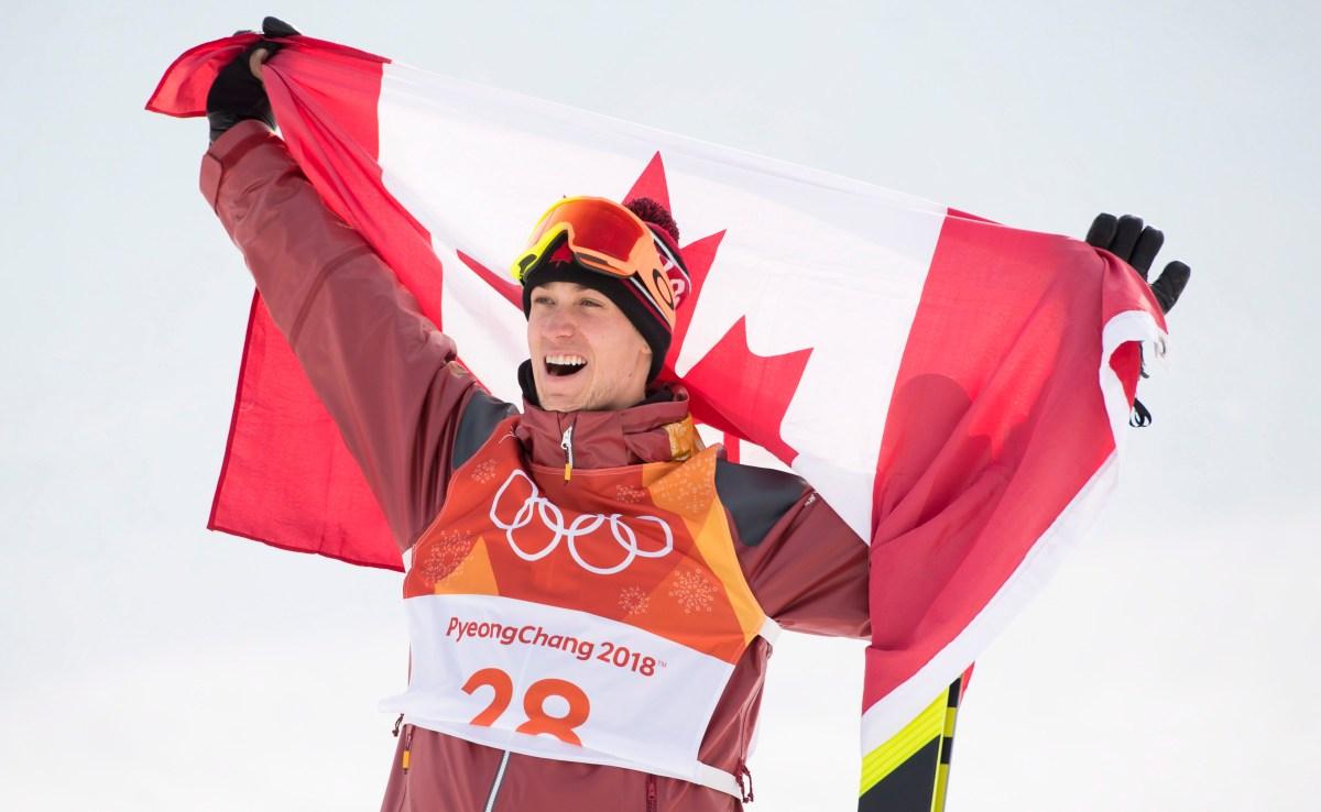 Alex Beaulieu-Marchand brandit le drapeau canadien après avoir remporté le bronze en ski slopestyle. LA PRESSE CANADIENNE/Jonathan Hayward