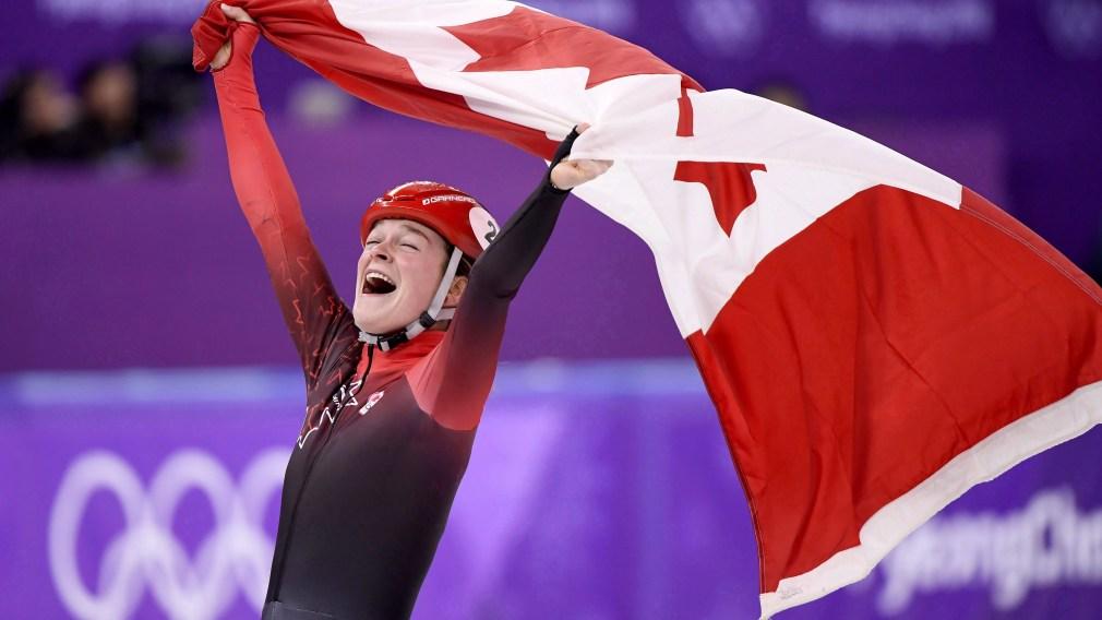 Kim Boutin célèbre en soulevant le drapeau canadien