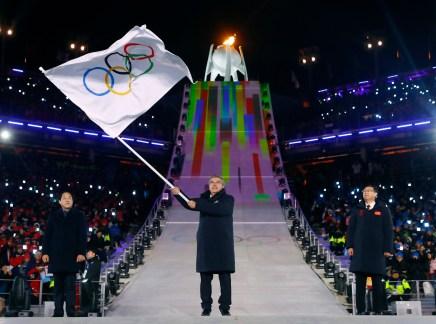 Le président du Comité olympique international, Thomas Bach, brandit le drapeau olympique, accompagné du maire de PyeongChang, Sim Jae-guk (gauche), ainsi que le maire de Beijing, Chen Jining (droite), lors de la cérémonie de clôture. (Kai Pfaffenbach/Pool Photo via AP)