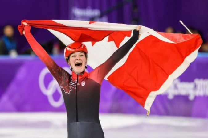 Kim Boutin défile avec le drapeau canadien après la course du 1500 m. (Photo par Vincent Ethier/COC)