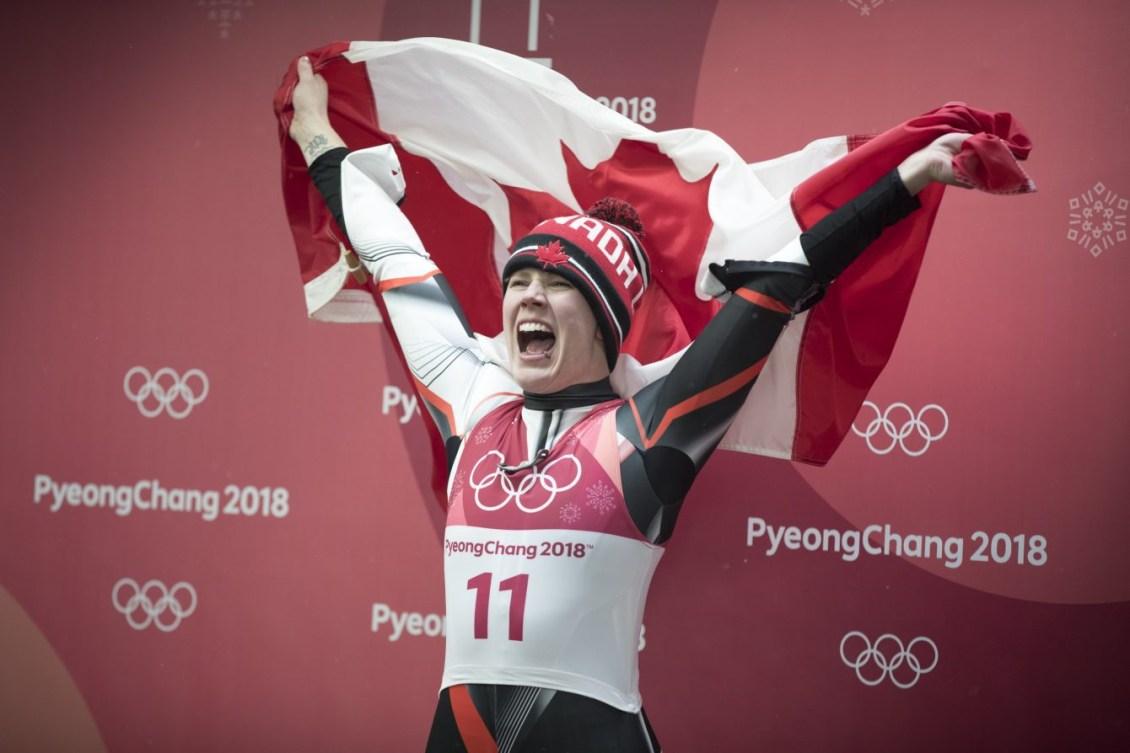 Alex Gough a un énorme sourire et tient le drapeau canadien
