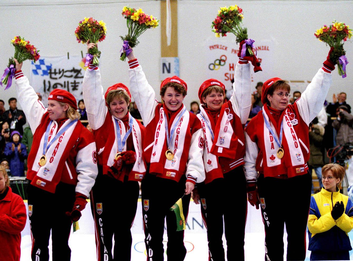Des athlètes sur le podium avec des bouquets de fleurs