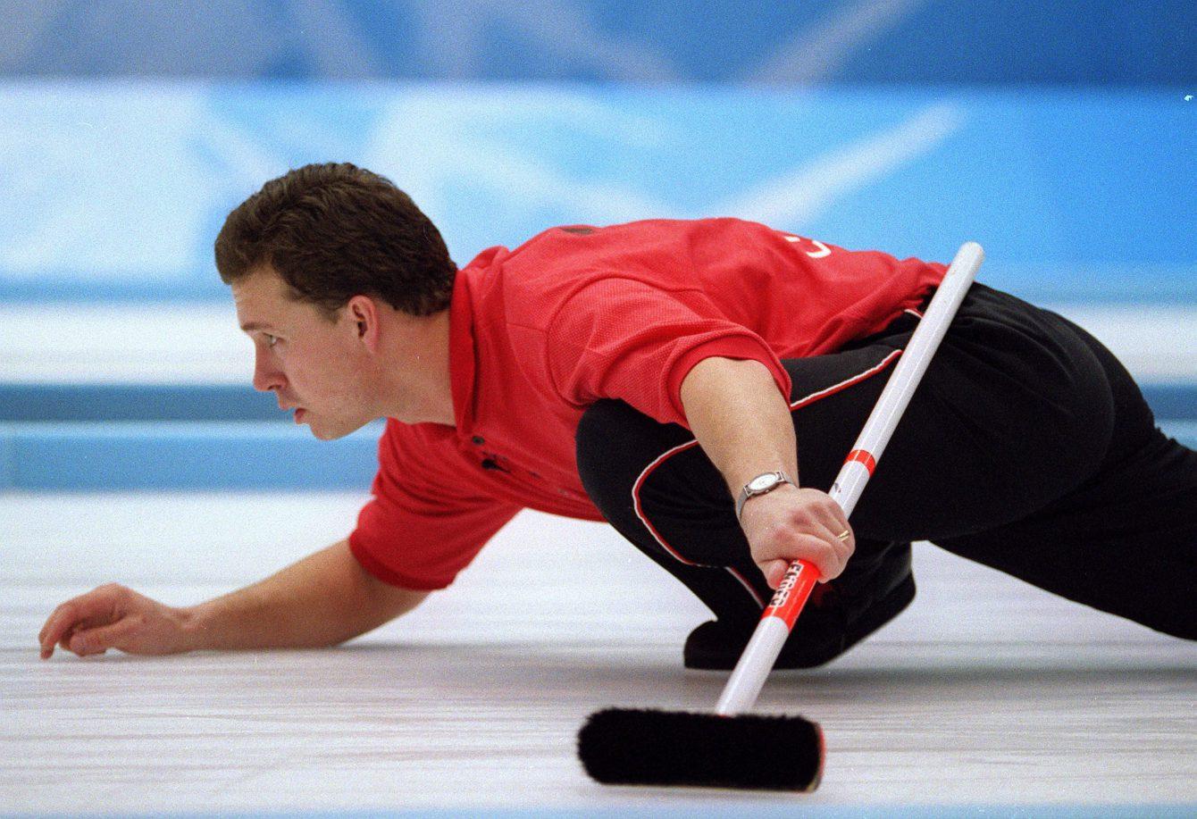 Un homme joue au curling